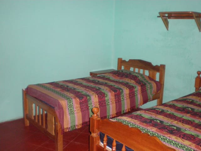 Bedroom with 2 single beds, shelves, fan, place to hang clothes.