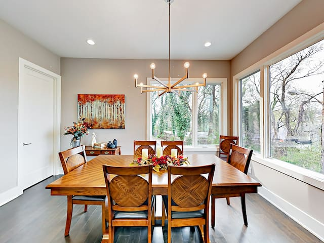 A modern chandelier hangs above the wood dining table.