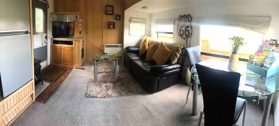 Reclining sofa, table and two chairs, Freesat TV including internet streaming access, Blu-ray player, electric convector heater and log burner