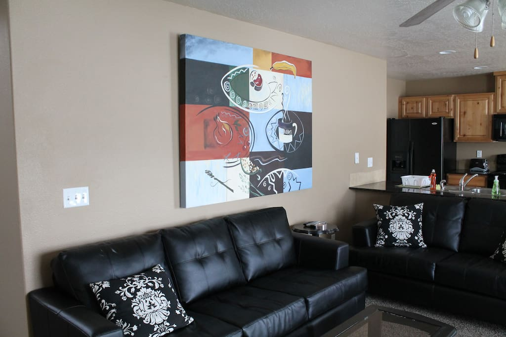 Living room with comfy leather sofas and ceiling fan.