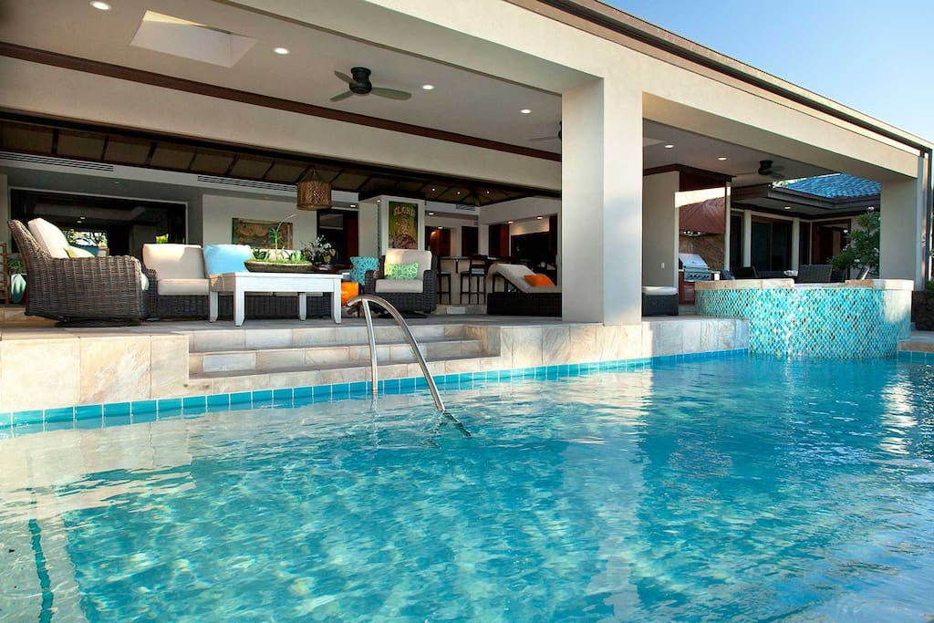 View of spacious covered lanai with ample seating from pool.