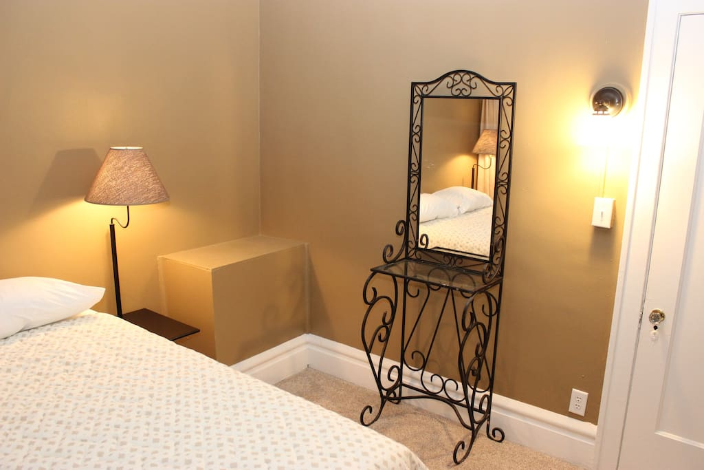 The bedroom includes a wrought-iron vanity and 2 side table/lamps.