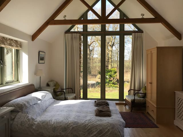 Master bedroom facing west and overlooking the garden and forest