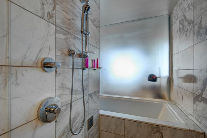 Rainfall shower glass head and jet tub in shower