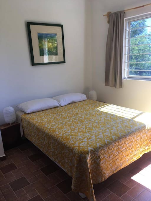 Queen sized bed in bright bedroom with beautiful view