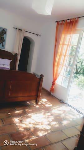 Votre chambre chez l'habitant avec salle de bain attenante privée et TV, donnant sur la piscine et sa terrasse arborée d'oliviers et de chênes verts.