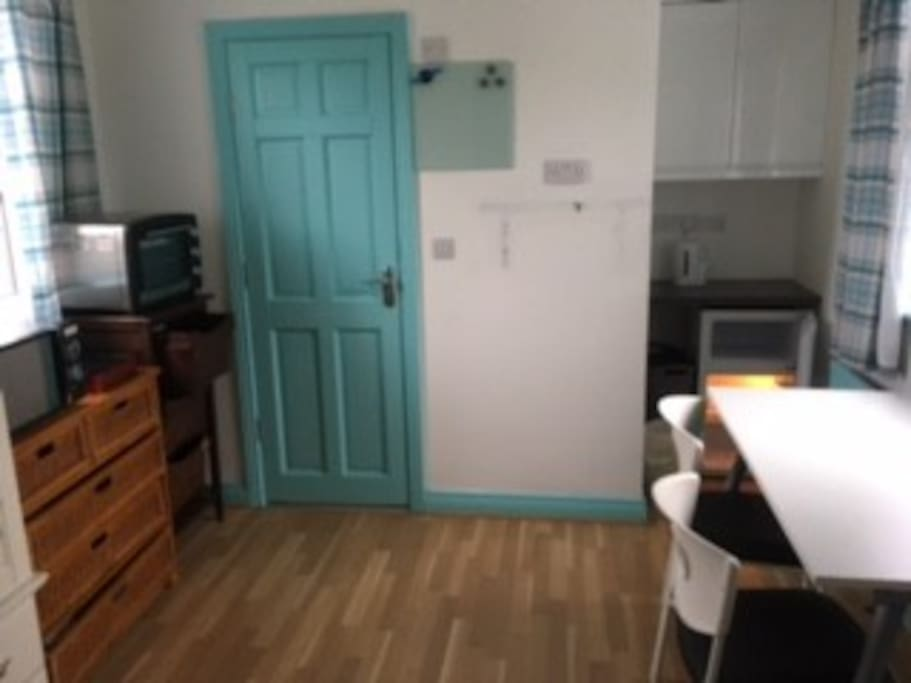 Main room Kitchenette with fridge/freezer, oven microwave, and induction hob.