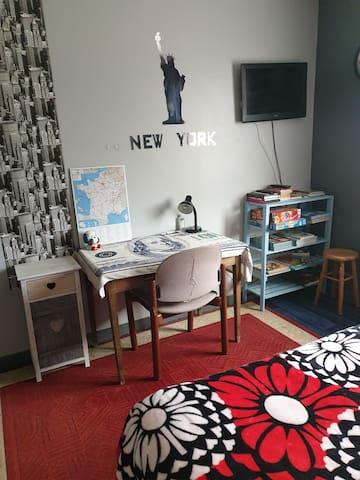Chambre avec télé et coin bureau
