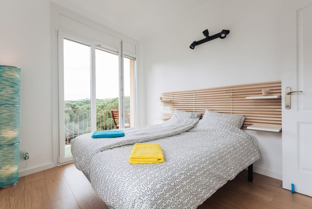 Queen size bed in a luminous room.