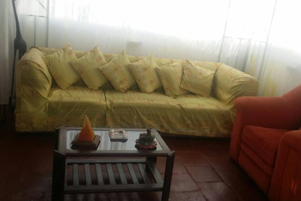 Esta es la sala, tiene un sofá de 4 cuerpos, 1 de un cuerpo y un puff