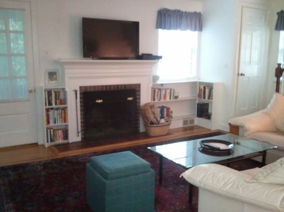 Living room, leather sotas, fireplace, books, HD TV, exit to screen porch