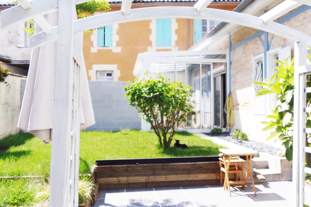 Accès au jardin par la terrasse de 25 m2. A droite de la terrasse, un cellier, pratique pour le rangement de matériel (accessoires plage, vélos etc..). Table et chaises d'extérieur.