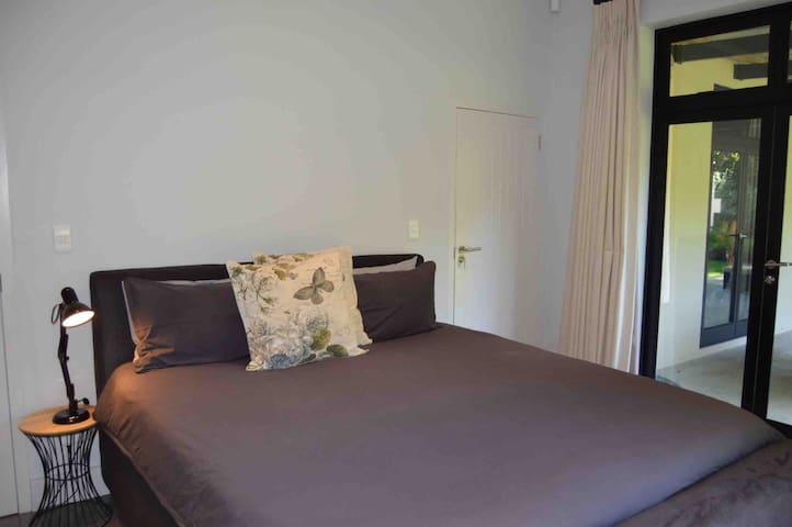King bed in main bedroom with bedside table and lamp