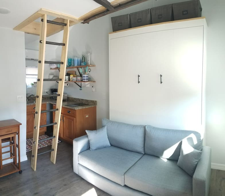 The white cabinet is actually a brand new queen size Murphy bed. Simply remove the couch cushions and pull down on the handles to set up the bed. Folds up and down easily with little effort.
