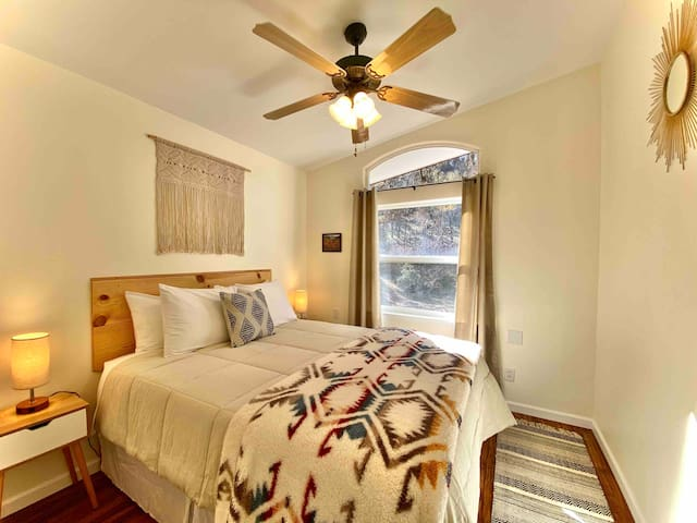 Bedroom 3 Large king bed.  All new beds and linens to enjoy.   Nice light and tree studded views.  Ceiling fan and lamps with USB ports.