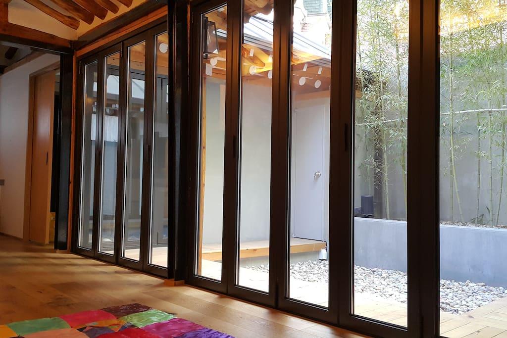 안으로 들어가면 대청마루가 있습니다. 마당이 보이게 전체가 이중유리로 되어있고 모두 활짝 열어져칠 수 있는 미닫이 창입니다.