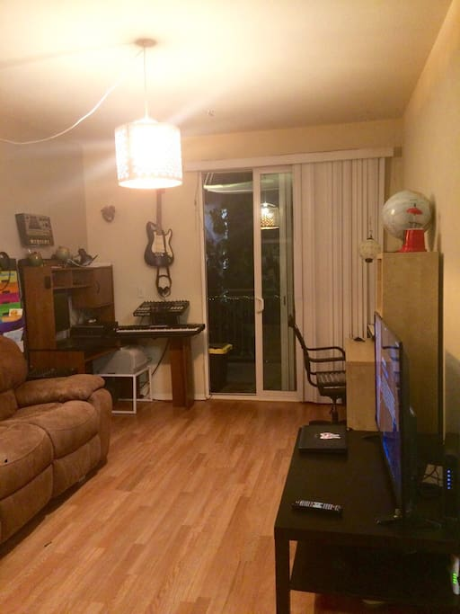 "Living room. All wood floors throughout place. 55"" Flat Screen TV with hundreds of cable channels including on demand. Plus roku ultra. Great balcony. Tropical landscaping."