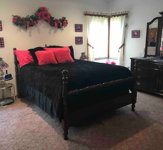 The large bedroom with queen sized bed is closest to the bathroom