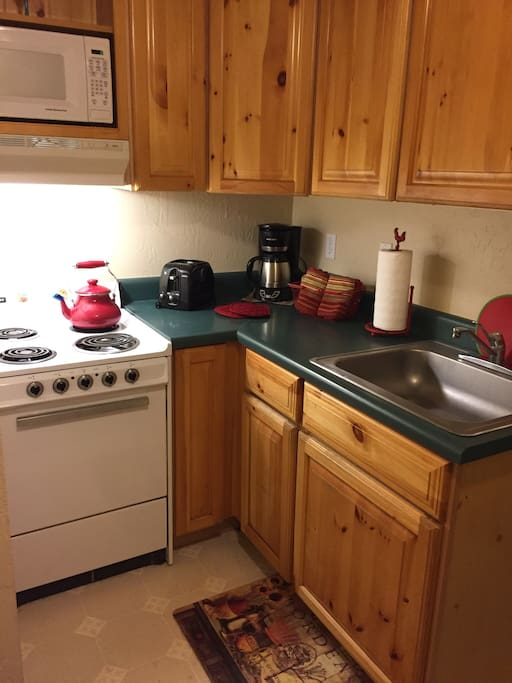 Kitchen includes stove, microwave and refrigerator.
