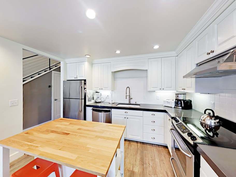 All the cookware, dishes, and utensils you need in this modern kitchen.