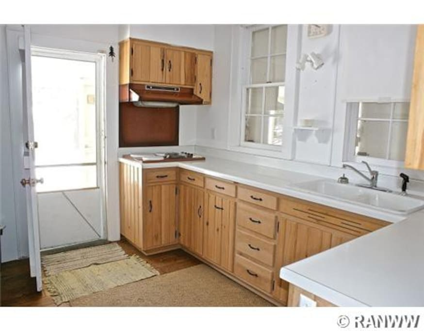 Kitchen has cooktop, sink, microwave, and fridge/freezer.