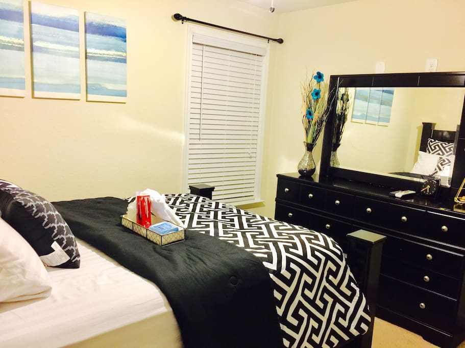 Guest private room showing a sturdy and very comfortable queen size bed set including a dresser & mirror & a bed stand. Guest will receive a small storage cart containing one brand new sponge, new toothbrush, toothpaste face & body towel & some wipes.