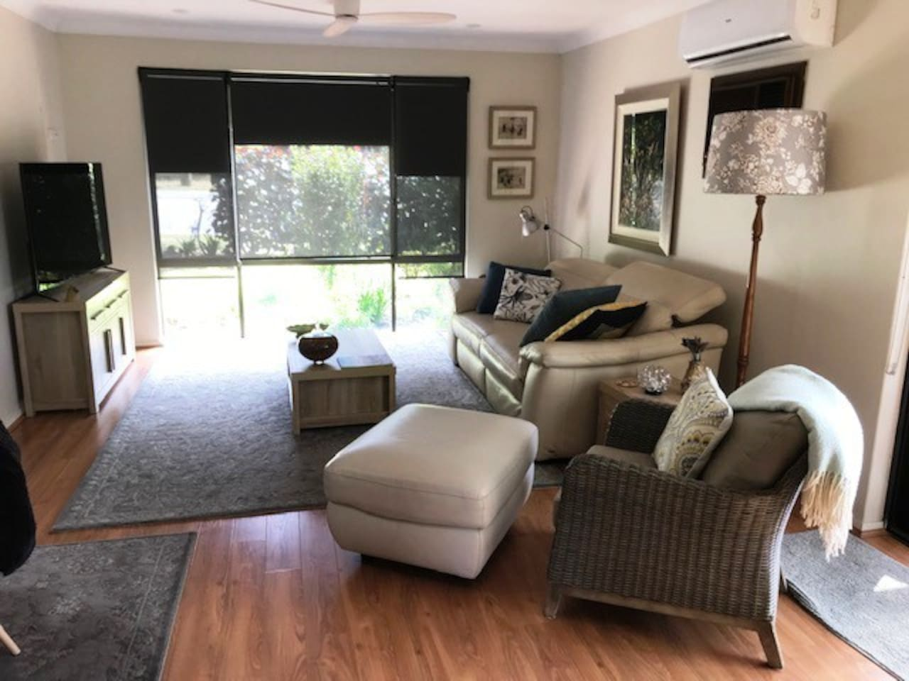 Welcome!  Lounge with reclining couch, soft lighting, smart TV, radio, original artwork, quality soft furnishings, view over garden and golf course beyond