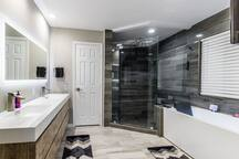 master room bathroom  with Jacuzzi bath led  20 inch rain shower head with 6 body sprays   dabble 80 inch vanity with a led mirror  large closet  and square toilet  43 inch tv and sound bar