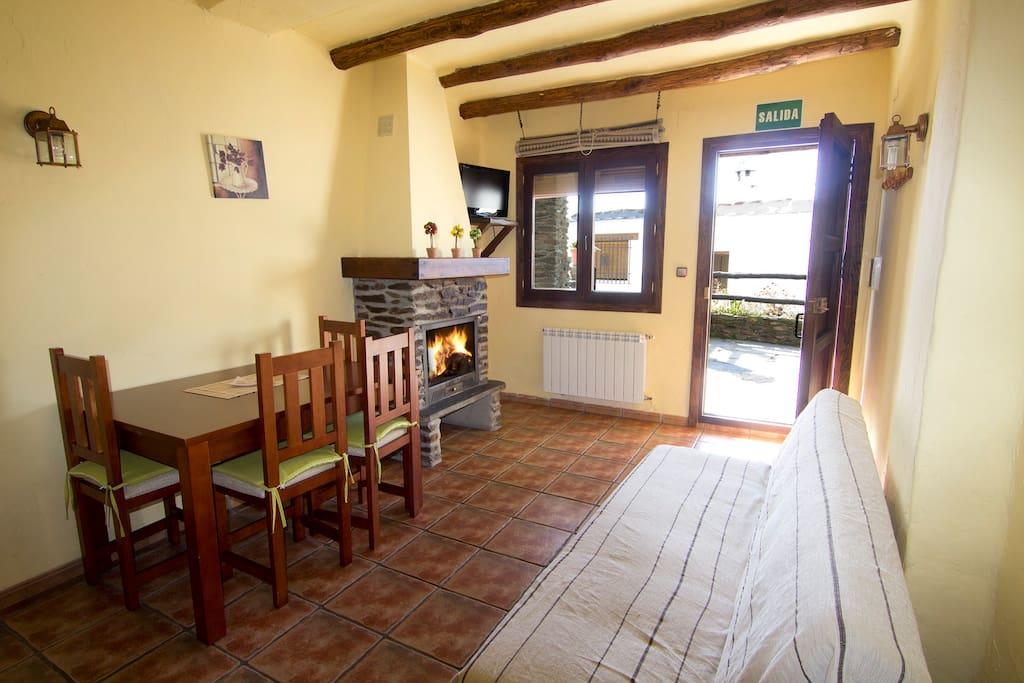 Salón-comedor con chimenea, calefacción y cocina.