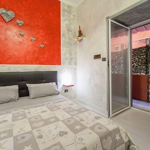Camera da letto con accesso alla veranda con tavolino e sedie per gustare una colazione classica napoletana