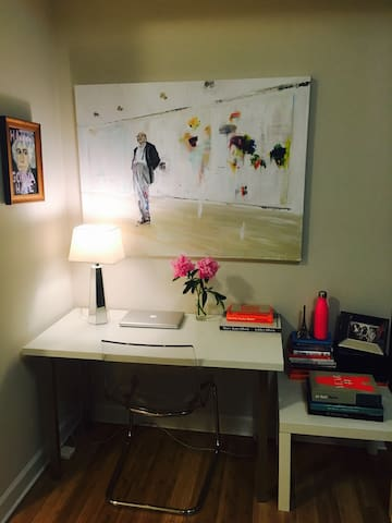 Desk space with a painting of Cy Twombly keeping watch.