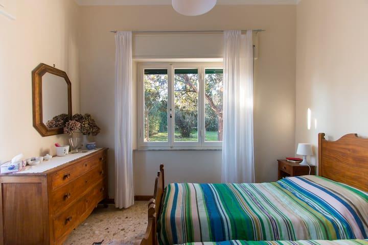 Camera matrimoniale con grosse finestre sul giardino