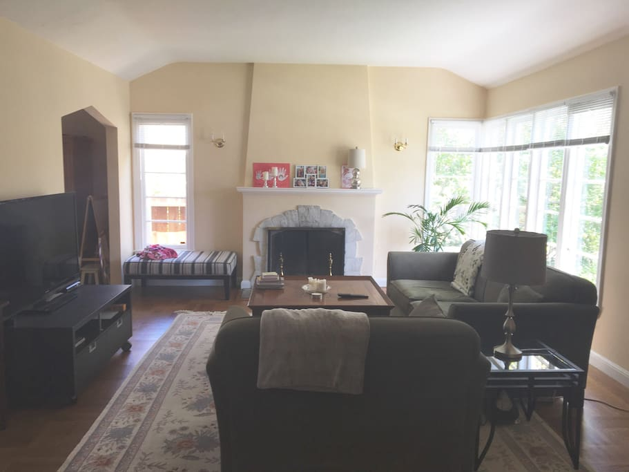 """Large living room with open fireplace, 55"""" TV and Apple TV."""