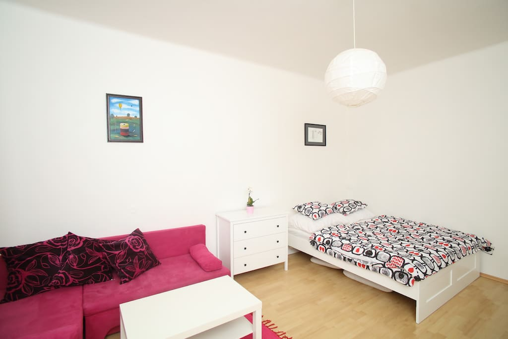 The living room features a double bed and a fold-out couch, dresser, dining table with four chairs and a stand-alone coat hanger. Using the fold-out couch, the flat sleeps up to 4 people. Pillows, covers and beddings are provided. Free WiFi is available throughout the flat.