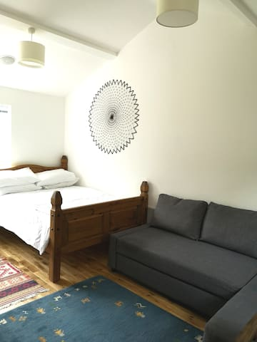 A bright and airy room with comfortable double bed and sofa bed.