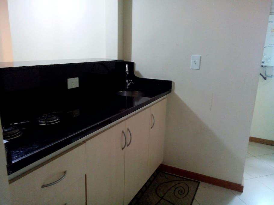 Cozinha equipada com fogão, geladeira, forno micro-ondas, louças, talheres e utensílios.