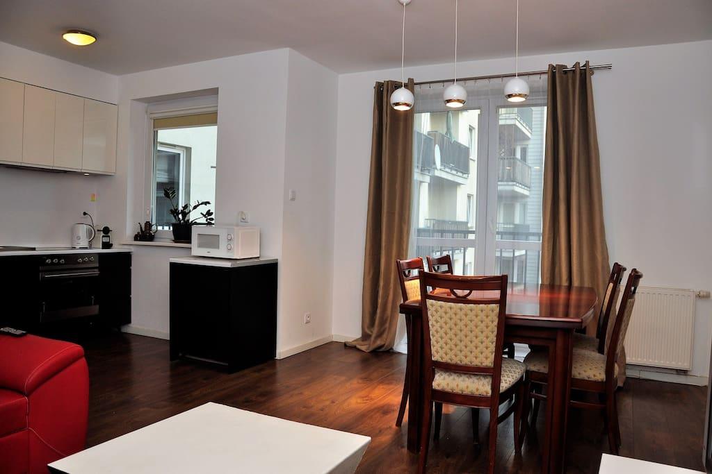 Pokój dzienny i stół, a po lewej stronie aneks kuchenny