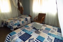Sunrise Cottage: Bedroom 2 with double bed and 1 single bed with shared shower + toilet, kitchen and veranda.
