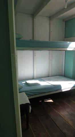 """Quarto privado """"Samba"""" para 1 ou 2 pessoas, com cama beliche, ventilador e janela com vista ao Clube do Samba que funciona de quinta a domingo até 23hs."""