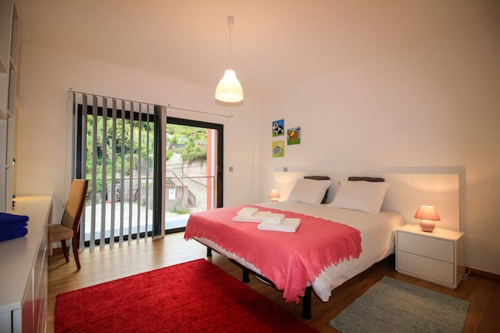 Bedroom with queen size bed and balcony access