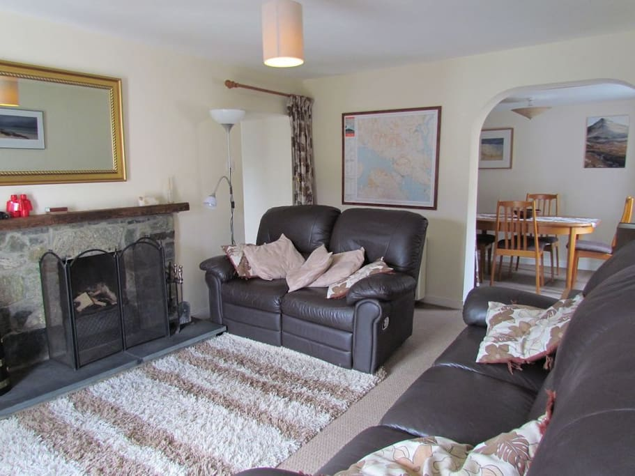 Living room with open fire (hand-crafted fireplace sourced from Harris stone) and patio door to garden.