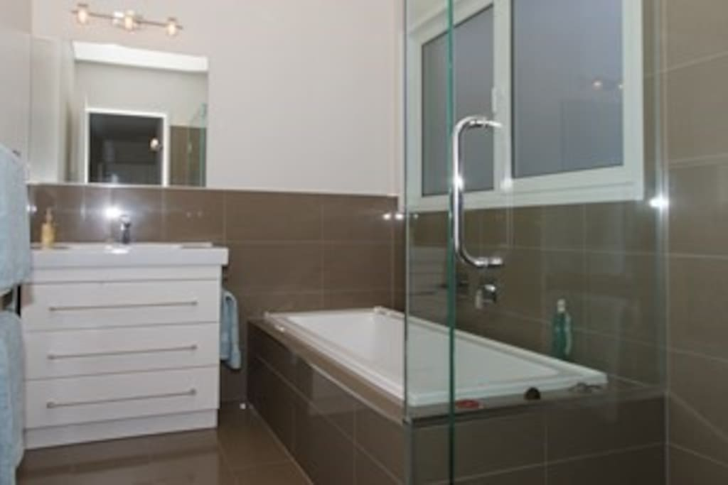 Bathroom with bath, separate shower and heated towel rail.