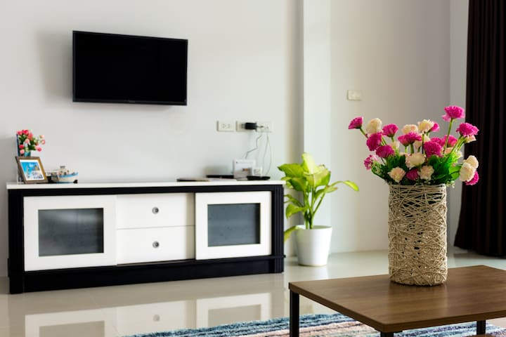 Living area with TV, sofa bed, table and flowerts