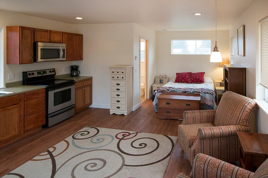 kitchen with full range, microwave hood, small fridge; queen size bed, dresser space