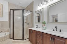 2nd master suite bath with double quartz vanity, travertine and shiplap jacuzzi tub and separate shower.