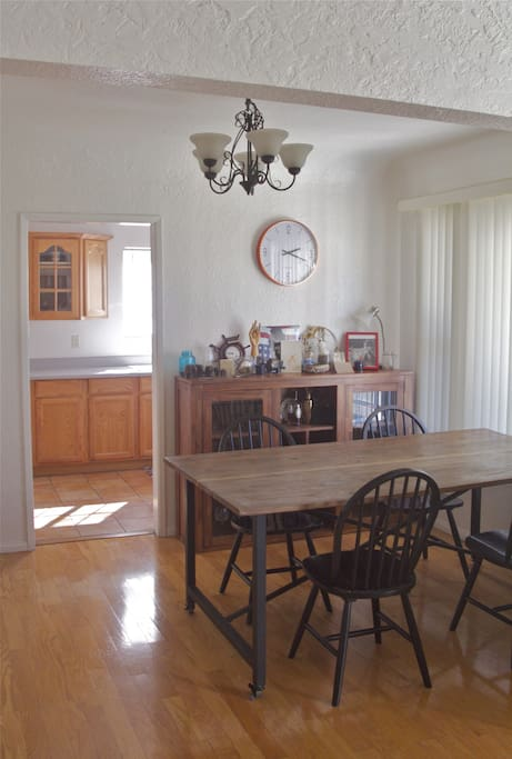 Large restored wood dining room table with huge windows through out living space.