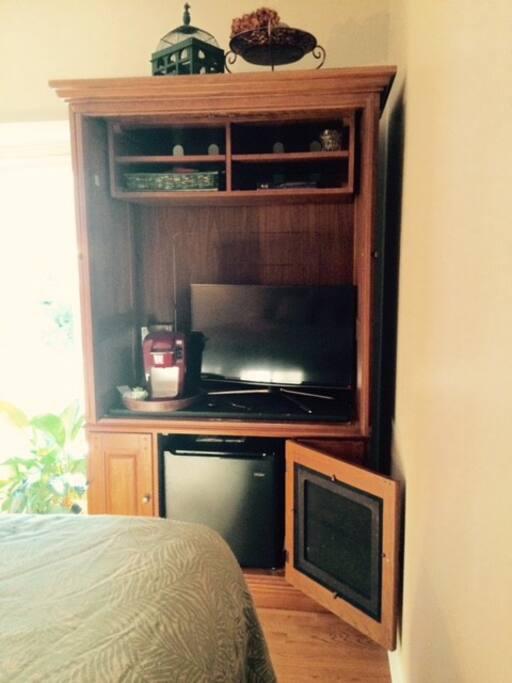 Flat screen, mini fridge, and keurig coffee machine