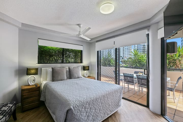 Master bedroom with queen bed, TV and patio access