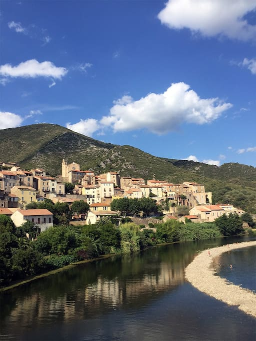 Roquebrun with its popular beach. Our house is located at the top of the village behind the church.