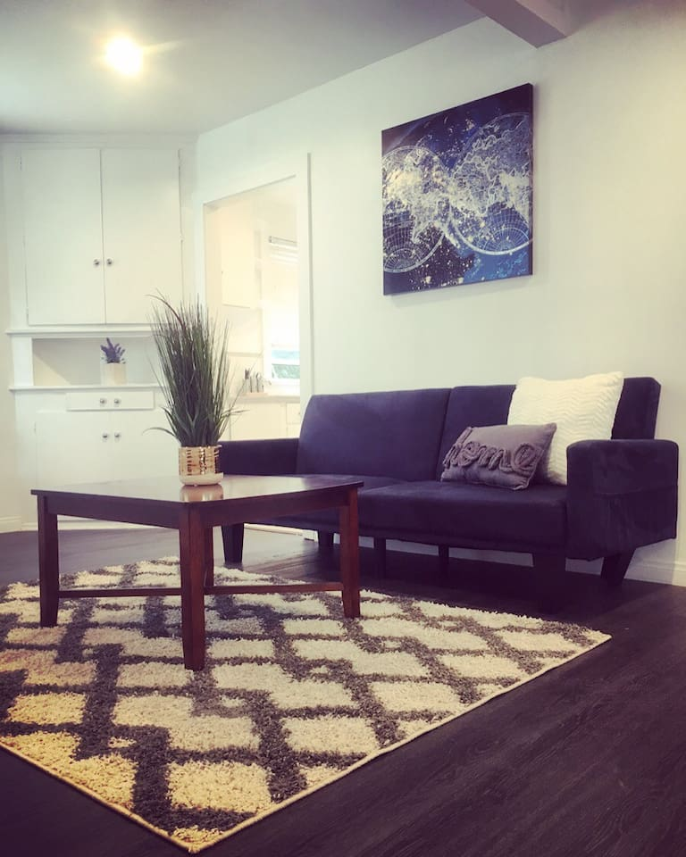 Large living area with brand new hardwood and tile floors throughout and recessed lighting.
